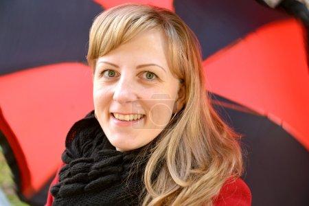 Photo pour Portrait de la jeune femme joyeuse contre un parapluie noir-rouge - image libre de droit