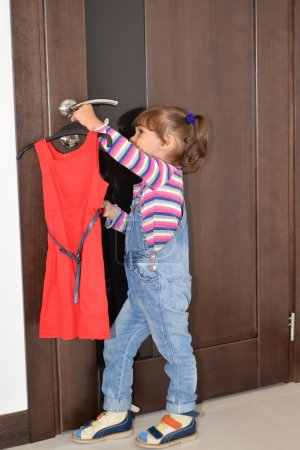 The three-year-old girl takes off from the door handle a beautif