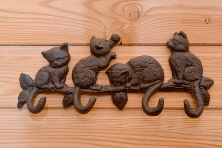 Metal hanger with hooks in the form of kittens on a wooden wall