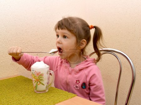 The little girl eats with a spoon oxygen cocktail. Phytobar of c