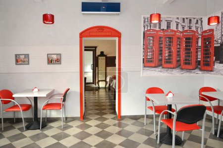 Interior of modern cafe in red and light tones. Stylization under the London landscape