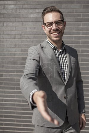 Businessman holds out his hand for handshake