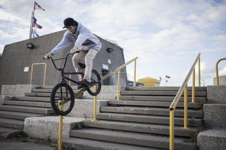 Bmx rider grinding on handrail