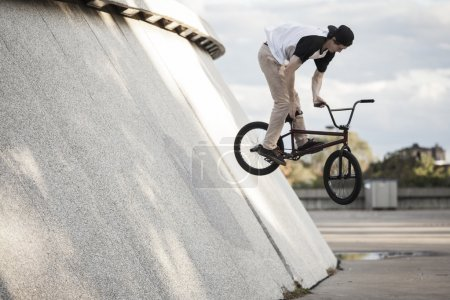 Young bmx rider doing a wallride