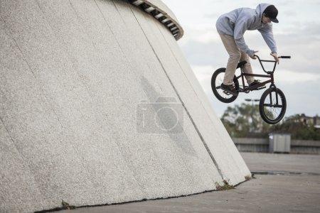 Young bmx rider doing a wallride