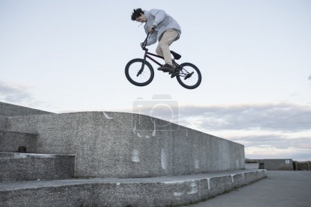 Bmx rider jumping off concrete wall