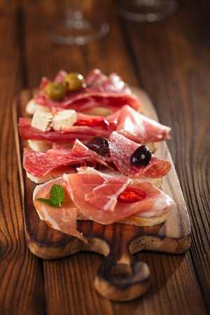 Photo for Antipasti Platter of Cured Meat,   jamon, olives, sausage, salami,  ciabatta and white wine glasses on textured wooden table - Royalty Free Image