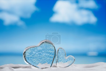 clear glass hearts on white sand beach