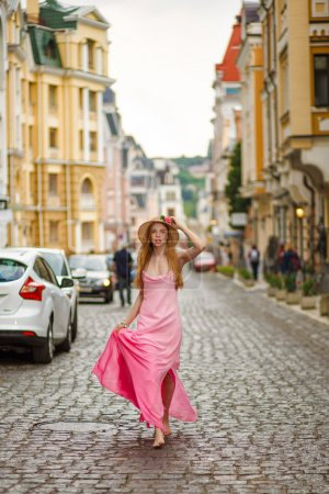 Artistic portrait of a young girl in the rain in a pink dress on