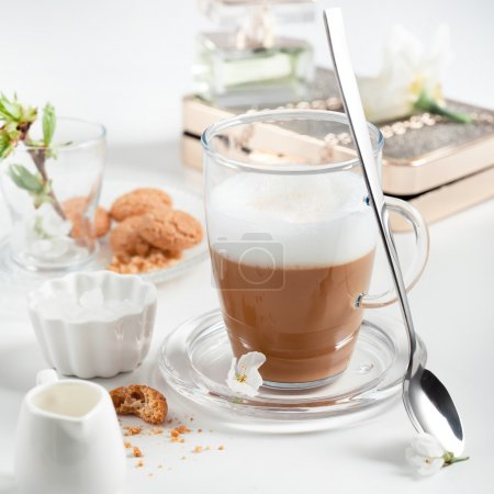 Cup of cappuccino set with cookies, cherry blossoms and perfume