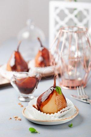 Pears in dark chocolate, sweet dessert, closeup shot