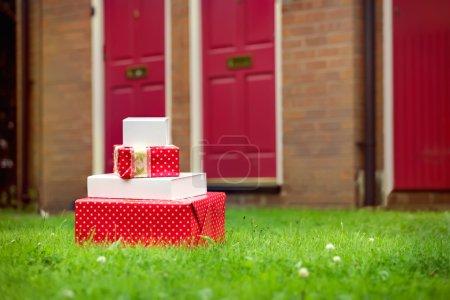 Photo pour Coffrets-cadeaux de Noël livré à la porte d'entrée de maison en été. début notion de préparation de Noël. - image libre de droit