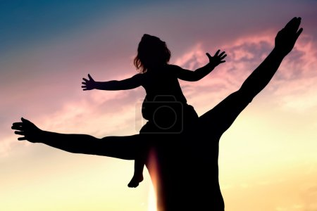 Photo for Silhouettes of father and daughter on his shoulders with hands up having fun, against sunset sky - Royalty Free Image