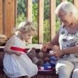 Little girl playing tea time with her grandmother ...