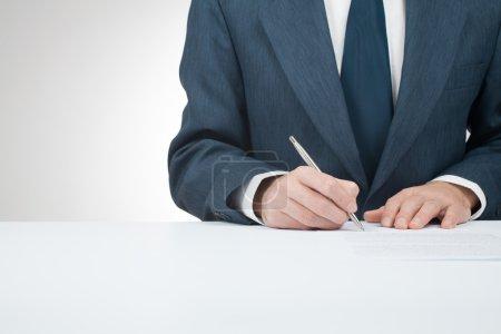 Photo pour Un homme d'affaires signe un contrat, un accord, une hypothèque, une assurance ou un autre document - image libre de droit