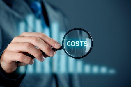Photo pour Mettre l'accent sur le concept de réduction des coûts. Homme d'affaires avec loupe agrandir word costs. Graphique avec diminution des coûts sur le fond - image libre de droit