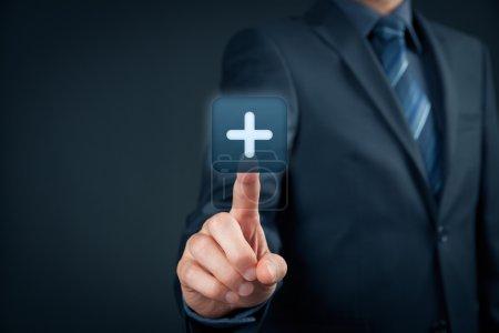 Photo pour Businessman clique sur le bouton plus, symbole de la chose positive comme les avantages, le développement personnel, les réseaux sociaux - image libre de droit
