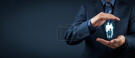 Photo pour Assurance vie familiale, services à la famille et concepts de soutien aux familles. Homme d'affaires avec geste protecteur et silhouette représentant une jeune famille. Composition de bannière large - image libre de droit