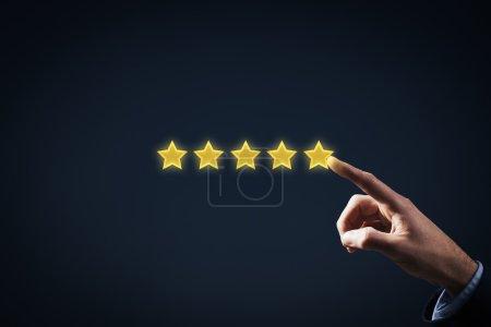 Photo pour Augmenter la notion de classification, d'évaluation et de notation. Homme d'affaires représenté à la main montée sur l'augmentation de cinq étoiles - image libre de droit
