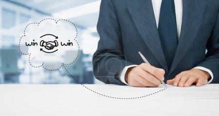 Photo pour Concept de stratégie de partenariat gagnant-gagnant. Un homme d'affaires signe un accord de stratégie gagnant-gagnant (contrat). Bureau en arrière-plan - image libre de droit