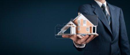 Photo pour Real estate agent offer house represented by model. Wide banner composition - image libre de droit