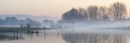 Foto de Paisaje hermoso panorama tranquilo lago en niebla - Imagen libre de derechos