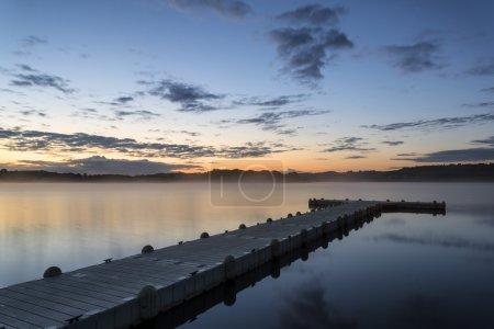 Photo for Sunrise landscape of jetty on calm lake - Royalty Free Image