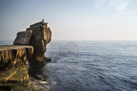 Beautiful rocky cliff landscape with sunset over ocean with undi