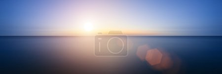 Photo for Conceptual image of sunrise sunset with added lens flare over still water ocean - Royalty Free Image