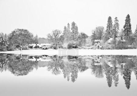 Black and white Winterr snow farm landscape reflected in frozen