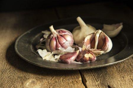 Photo pour Gousses d'ail fraîches avec un éclairage naturel moody, mis en place avec style vintage - image libre de droit