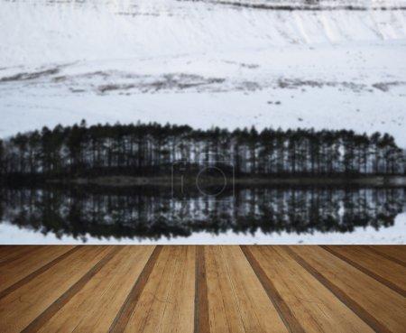 Photo pour Forêt et montagne Paysage hivernal reflété dans les eaux calmes du lac avec planches de bois - image libre de droit