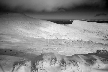 Foto de Impresionante paisaje de montañas cubiertas de nieve en invierno en blanco y negro - Imagen libre de derechos