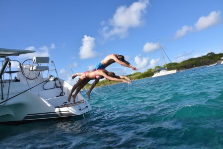 Couple diving from sailboat