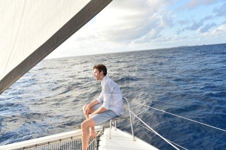 Photo pour Beau homme relaxant sur un voilier au milieu de la mer - image libre de droit