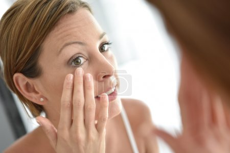 Photo for Woman applying facial cream on her face - Royalty Free Image