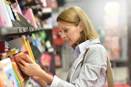 Photo pour Client de femme shopping dans le magasin de livre - image libre de droit