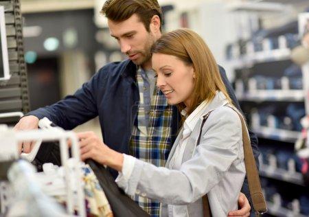 Photo pour Couple faisant du shopping ensemble dans un magasin de vêtements - image libre de droit