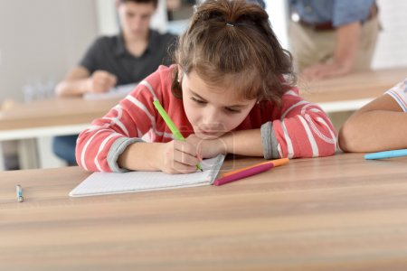 schoolgirl in class writing on notebook