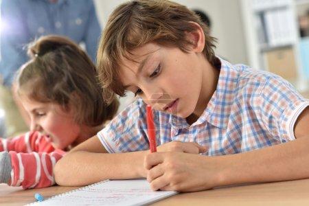 School boy in class writing