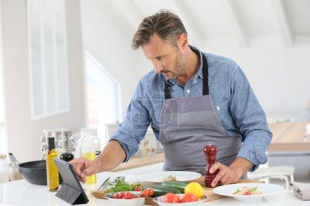 Man in kitchen cooking dish