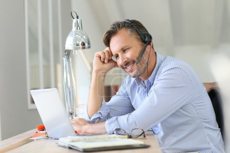 Photo for Businessman teleworking with  headset on while sitting at desk - Royalty Free Image