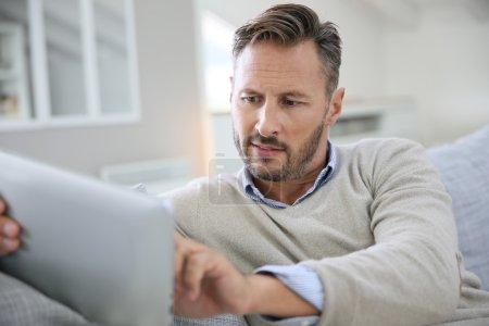 man at home websurfing on digital tablet