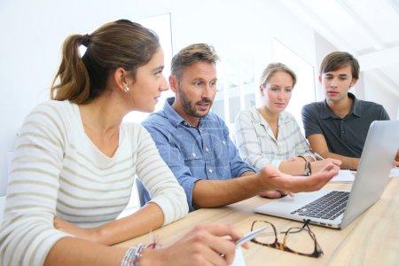 Photo pour Enseignant avec un groupe d'étudiants travaillant sur un ordinateur portable - image libre de droit