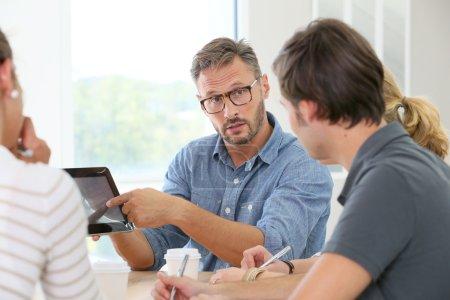 Photo pour Enseignant avec groupe d'étudiants travaillant sur tablette numérique - image libre de droit