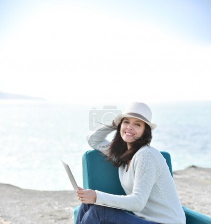 Woman with hat on  sitting by the sea
