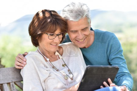 couple using tablet on yard