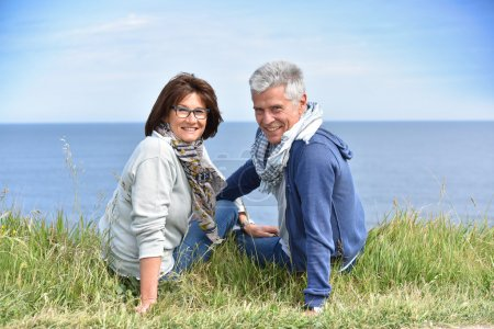 Photo for Mature couple on rambling day sitting by cliff - Royalty Free Image