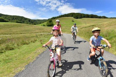 Photo pour Happy famille à vélo dans la route de montagne - image libre de droit