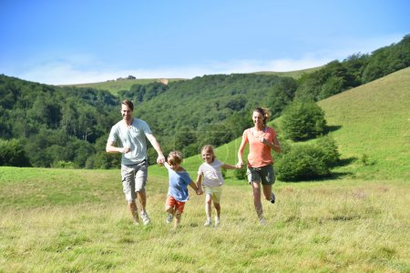 Photo for Family on vacation running down the hill - Royalty Free Image